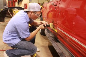 Student in Collision Repair working on a car