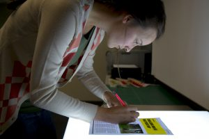 Digital Media student looking at light board