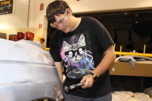 student working on wrecked car in collision repair
