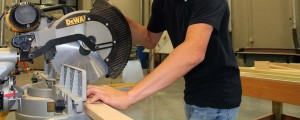 Close up of Carpentry student cutting a board