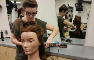 Student working on a manikin in the salon