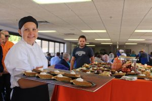 Student serving pumpkin pie at Thanksgiving Luncheon